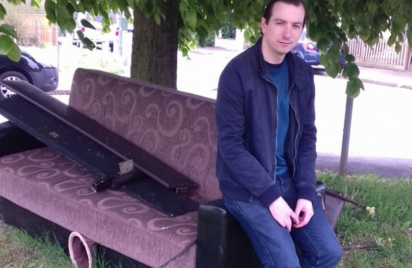 Ross Archer on a discarded sofa